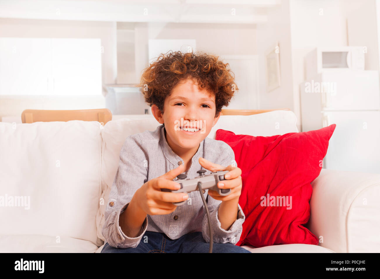 Portrait of preadolescent boy, sitting with joystick on the sofa and playing video games - Stock Image