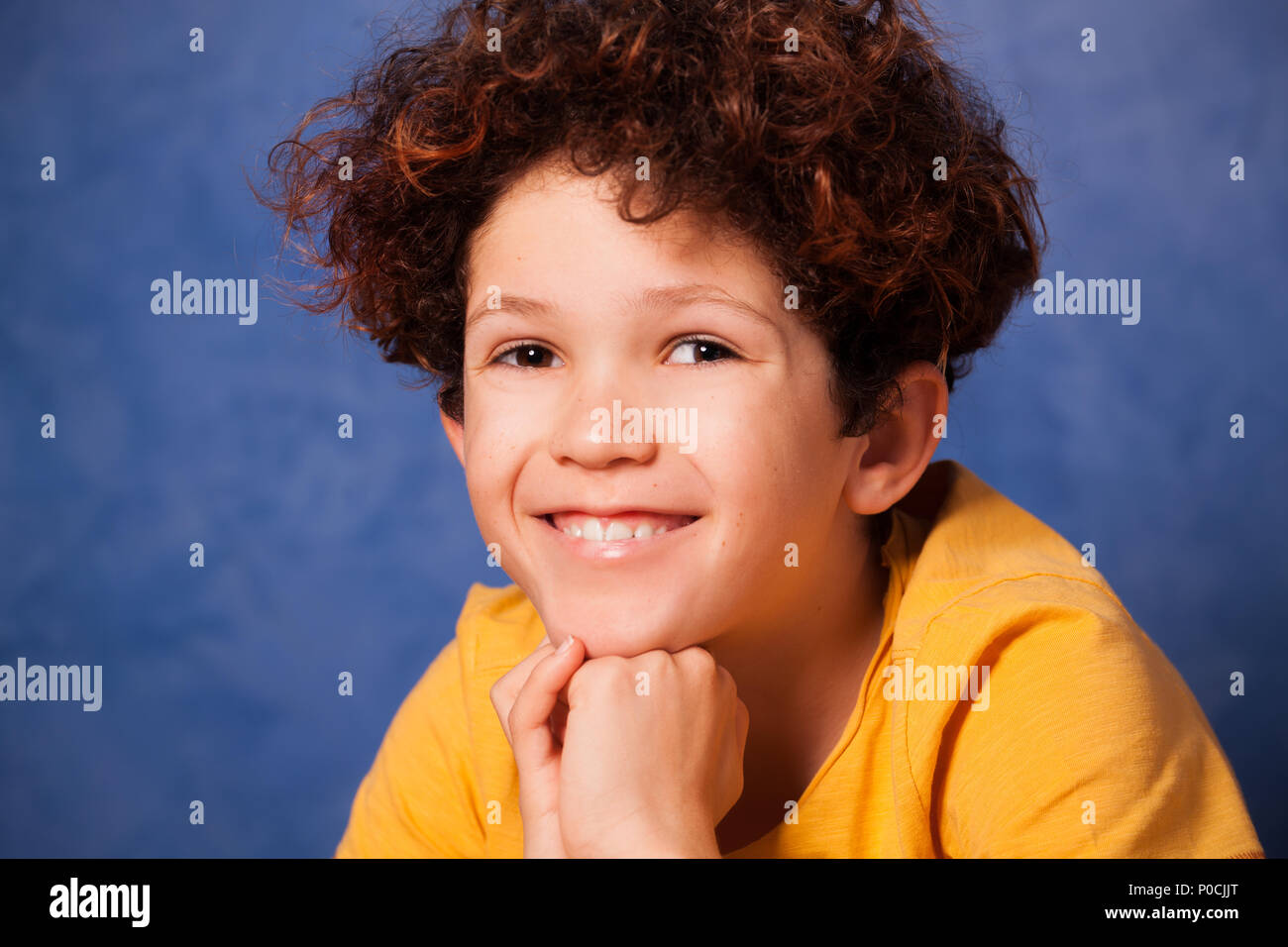 Portrait of happy young boy with curly hair against blue background - Stock Image