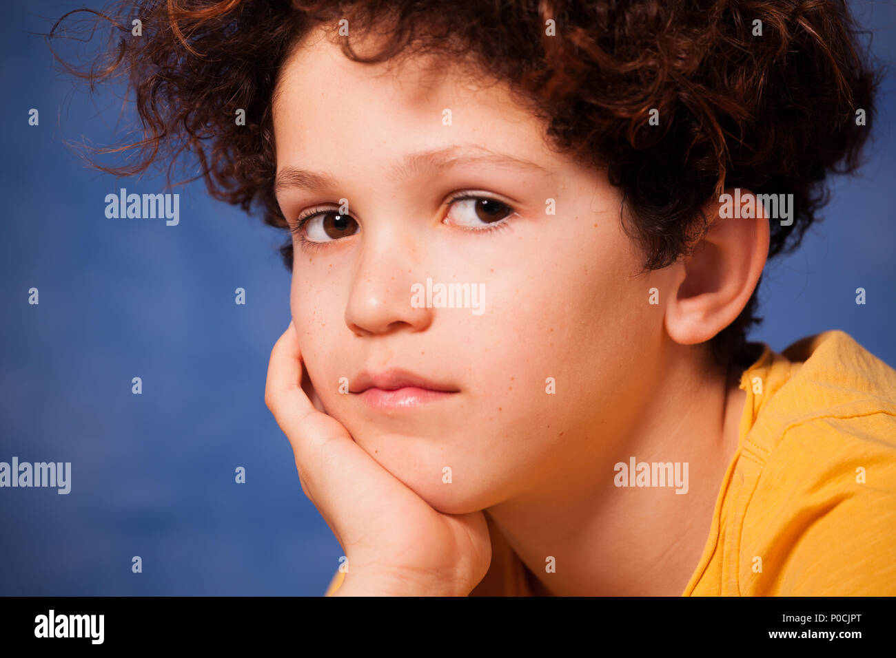 Close-up portrait of thoughtful preteen boy looking at camera - Stock Image