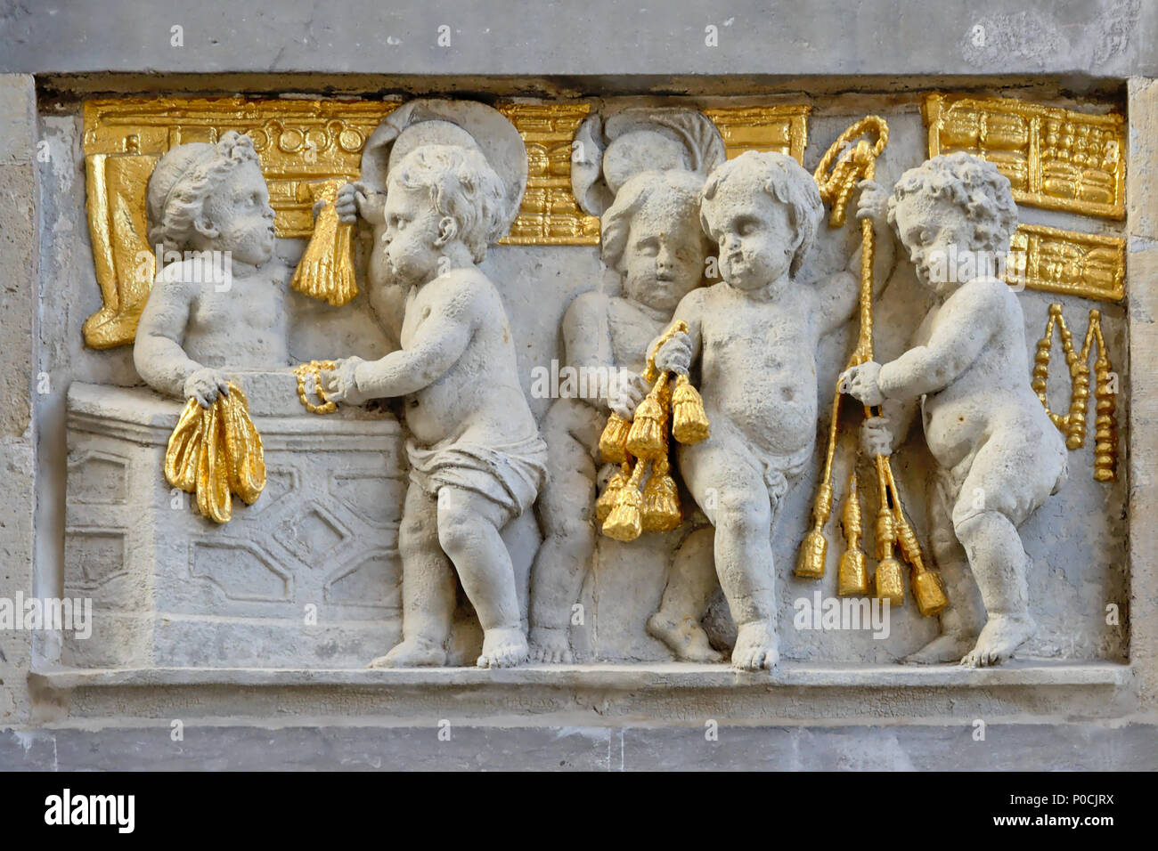 Bas relief in stone and gold of cherubs producing textile, found on the facade of a medieval house on Brussels Grand Place square - Stock Image