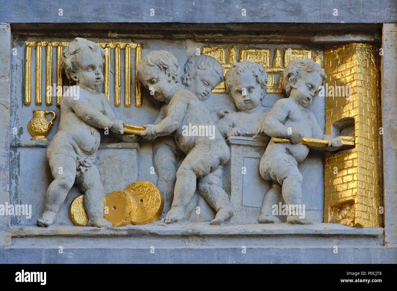 Bas relief in stone and gold of cherubs at work, found on the facade of a medieval house on Brussels Grand Place square - Stock Image