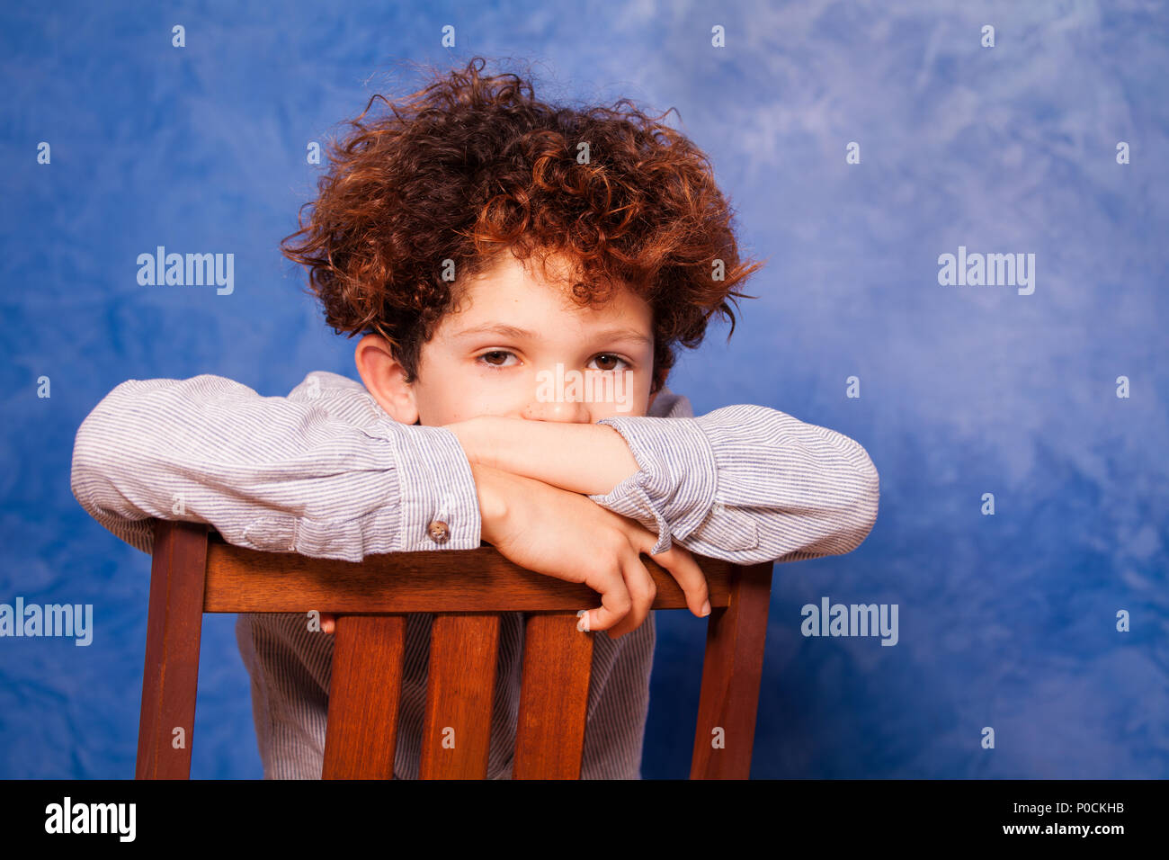 Portrait of cute boy with curly hair sitting backwards on wooden chair against blue background and looking at camera - Stock Image