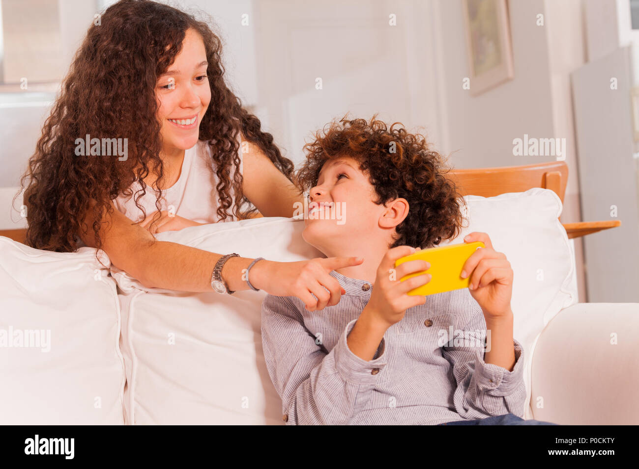 Portrait of teenage boy and girl chatting using cell phone, sitting on coach in light living room - Stock Image