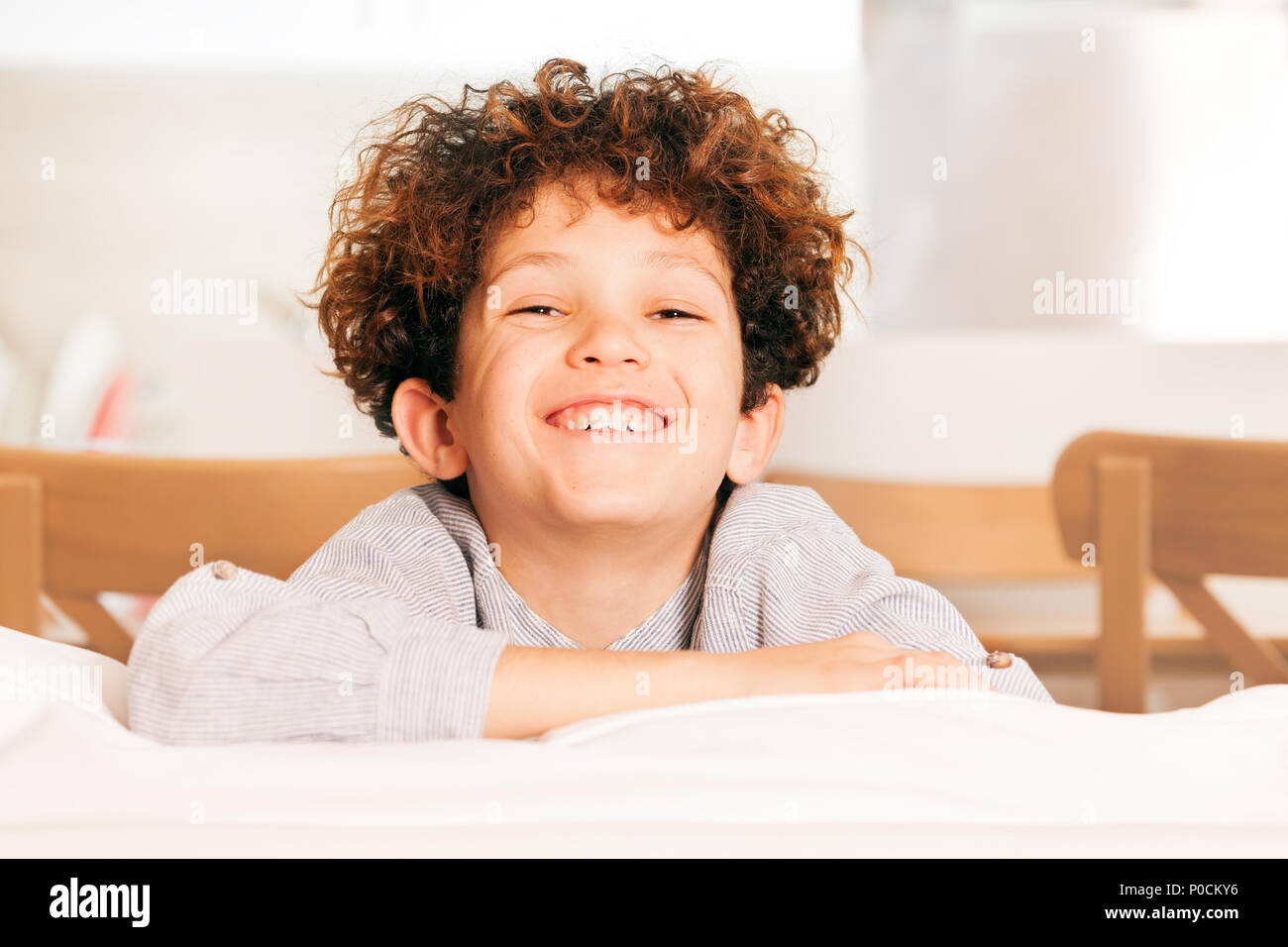 Portrait of cute young boy with curly hair sitting on the couch, laughing and looking at camera - Stock Image