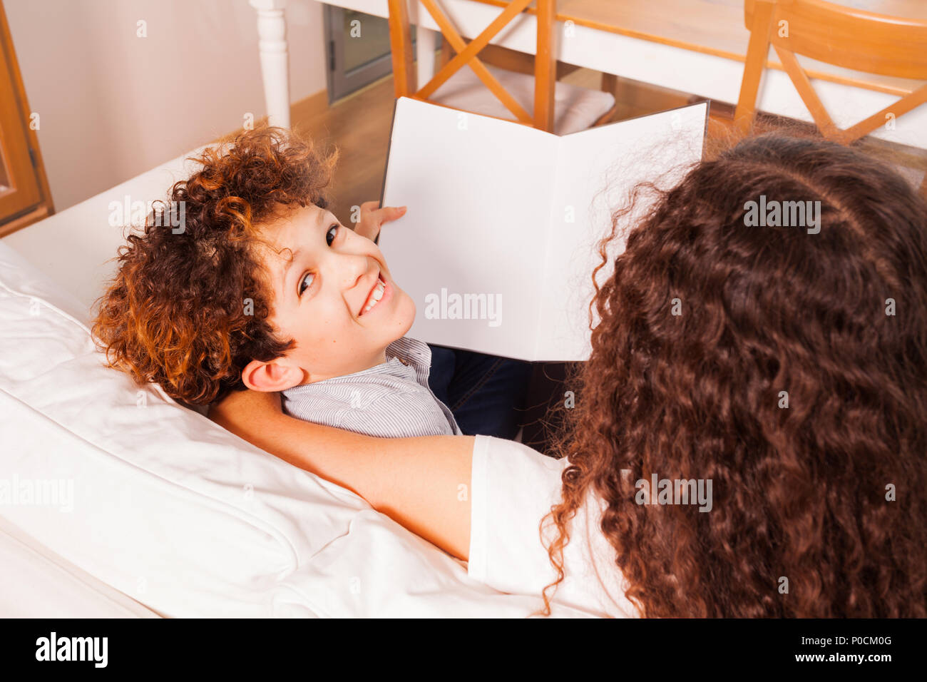 Top view of happy preteen boy reading book, sitting in home interior on the couch - Stock Image