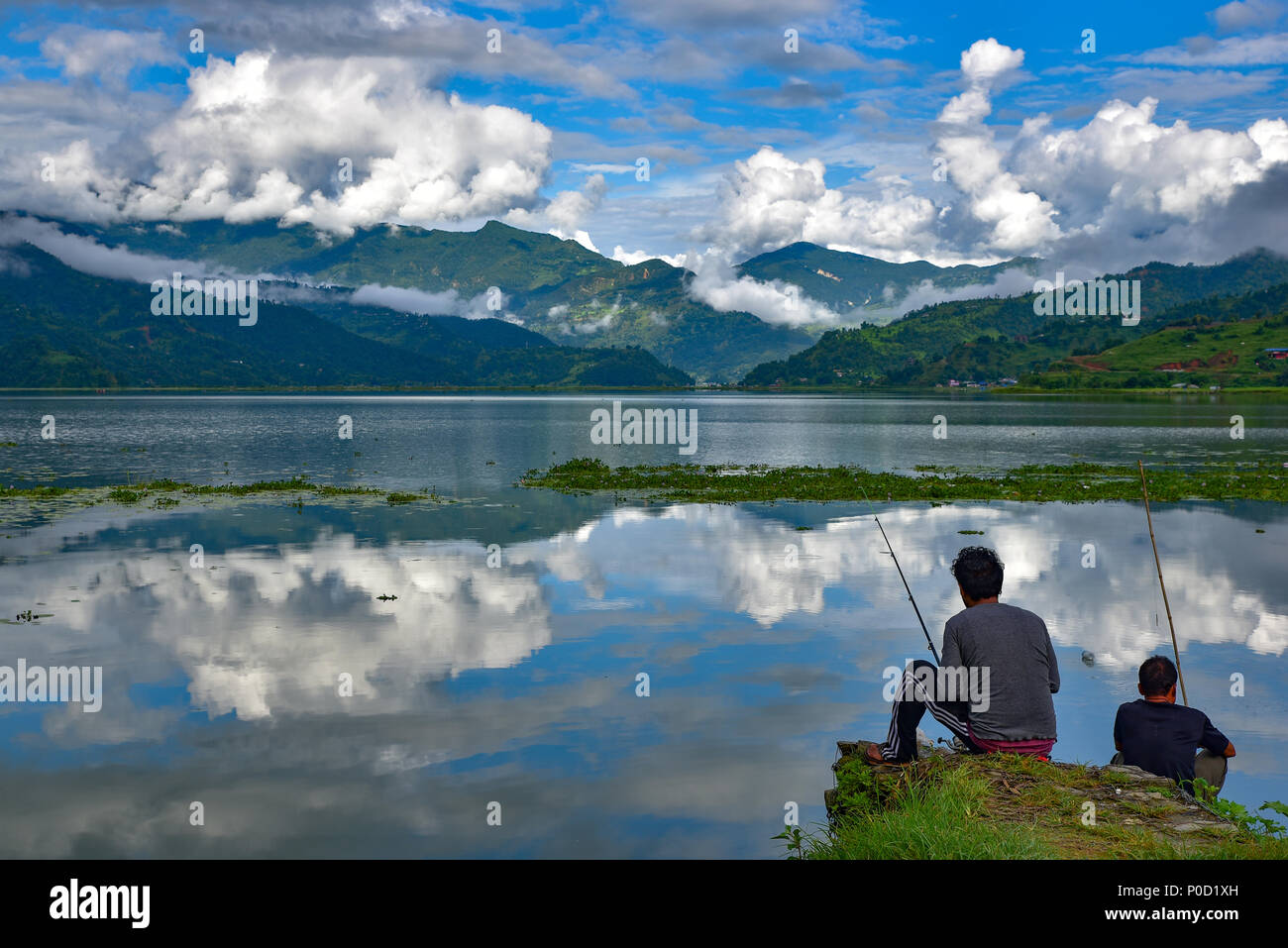 Two men fishing at Fewa Lake, Pokhara, Nepal - Stock Image