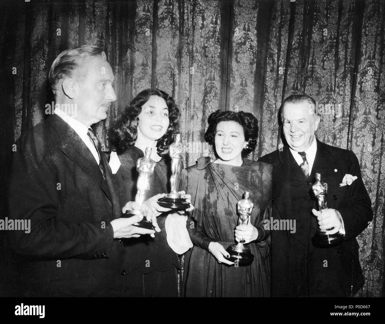 Description: The 16th Academy Awards / 1944.   Paul Lukas, best actor for 'Watch on the Rhine'. Jennifer Jones, best actress for 'The Song of Bernadette'. Katina Paxinou, best actress in a supporting role for 'For Whom the Bells Tolls'. Charles Coburn, best actor in a supporting role for  'The More the Merrier'..  Year: 1944.  Stars: PAUL LUKAS; CHARLES COBURN; KATINA PAXINOU; JENNIFER JONES. - Stock Image