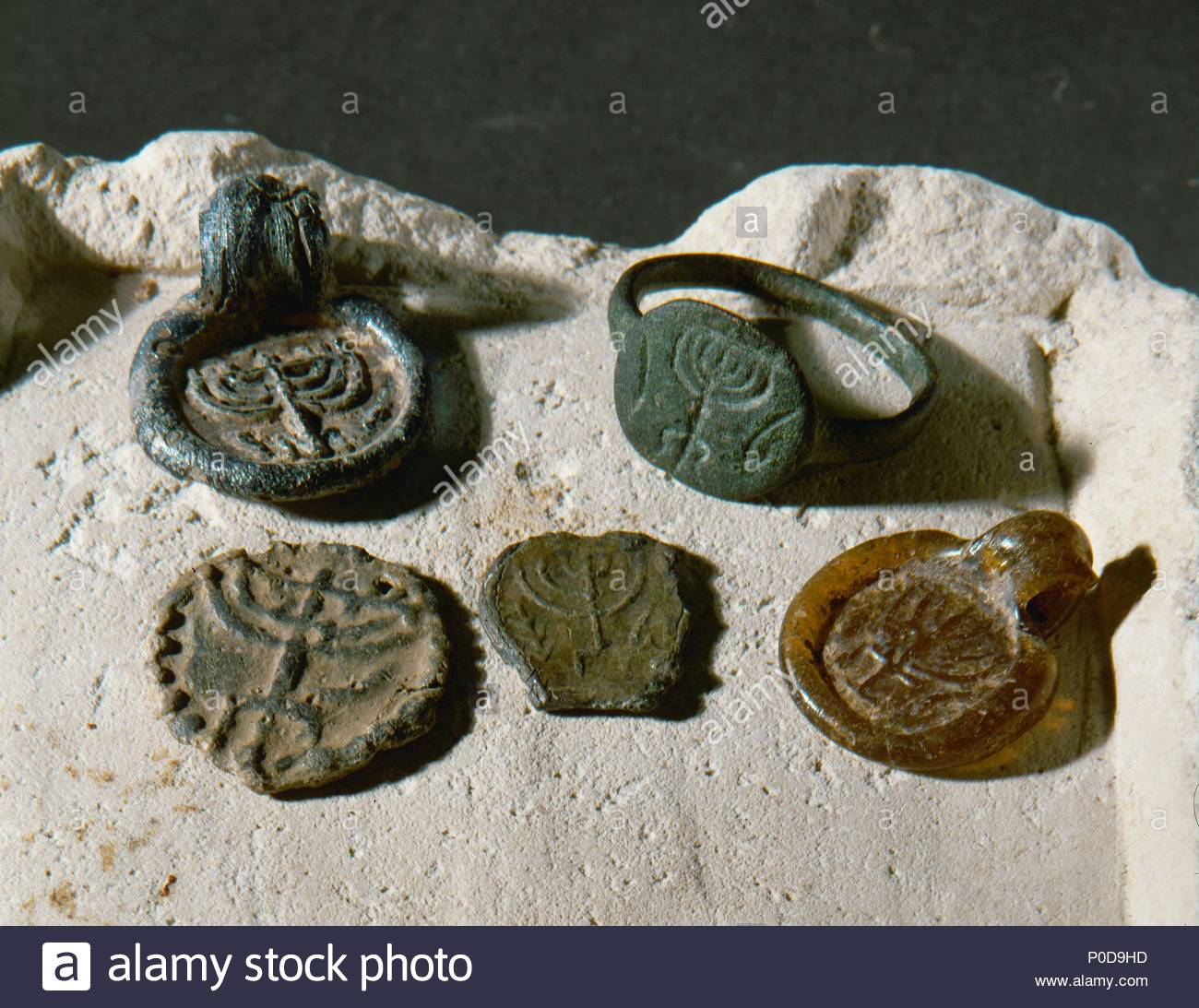 Seal ring with menorah design, bronze (4th CE); Byzantine medallions, glass and lead (2nd-3rd CE) Roman; Jewish teressa coin, lead (2nd CE) Roman. Location: Haaretz Museum, Tel Aviv, Israel. - Stock Image