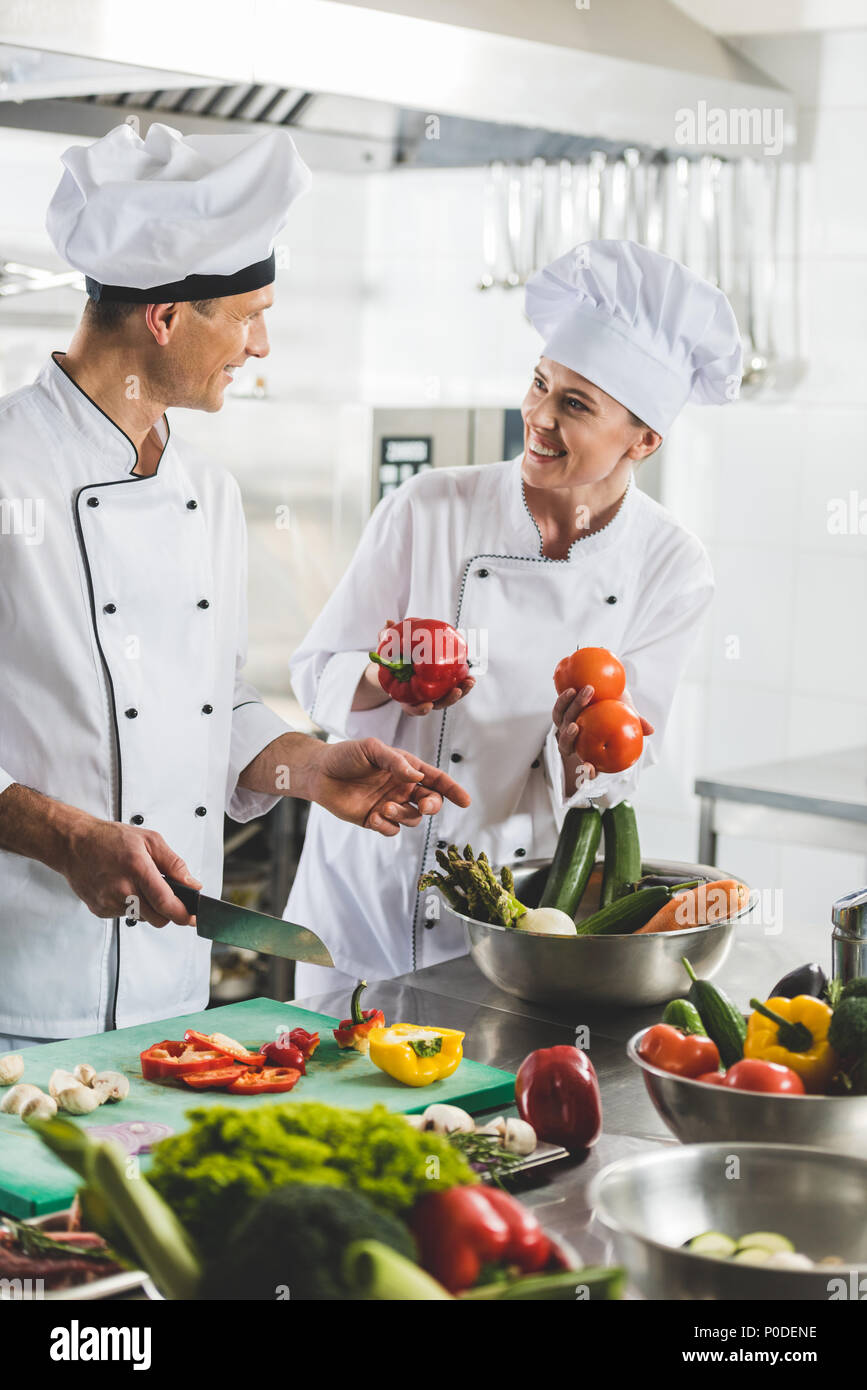 smiling chefs cooking and looking at each other at restaurant kitchen - Stock Image