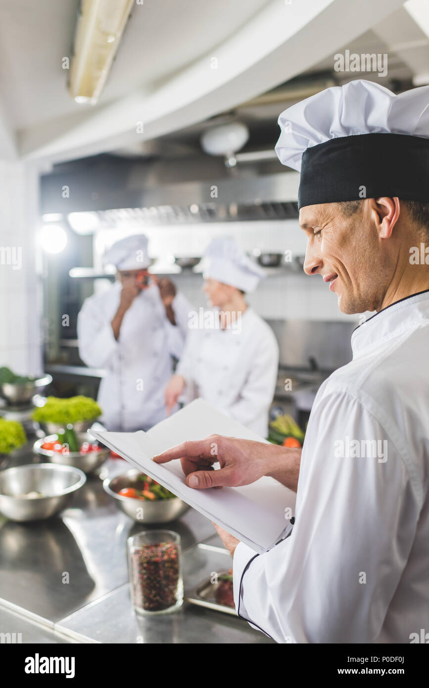 side view of chef pointing on recipe book at restaurant kitchen