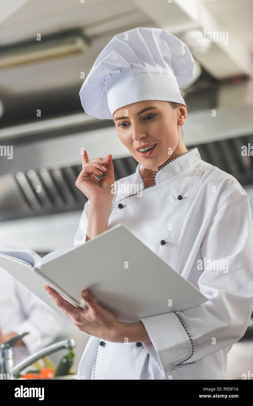 attractive chef reading recipe and showing idea gesture at restaurant kitchen - Stock Image