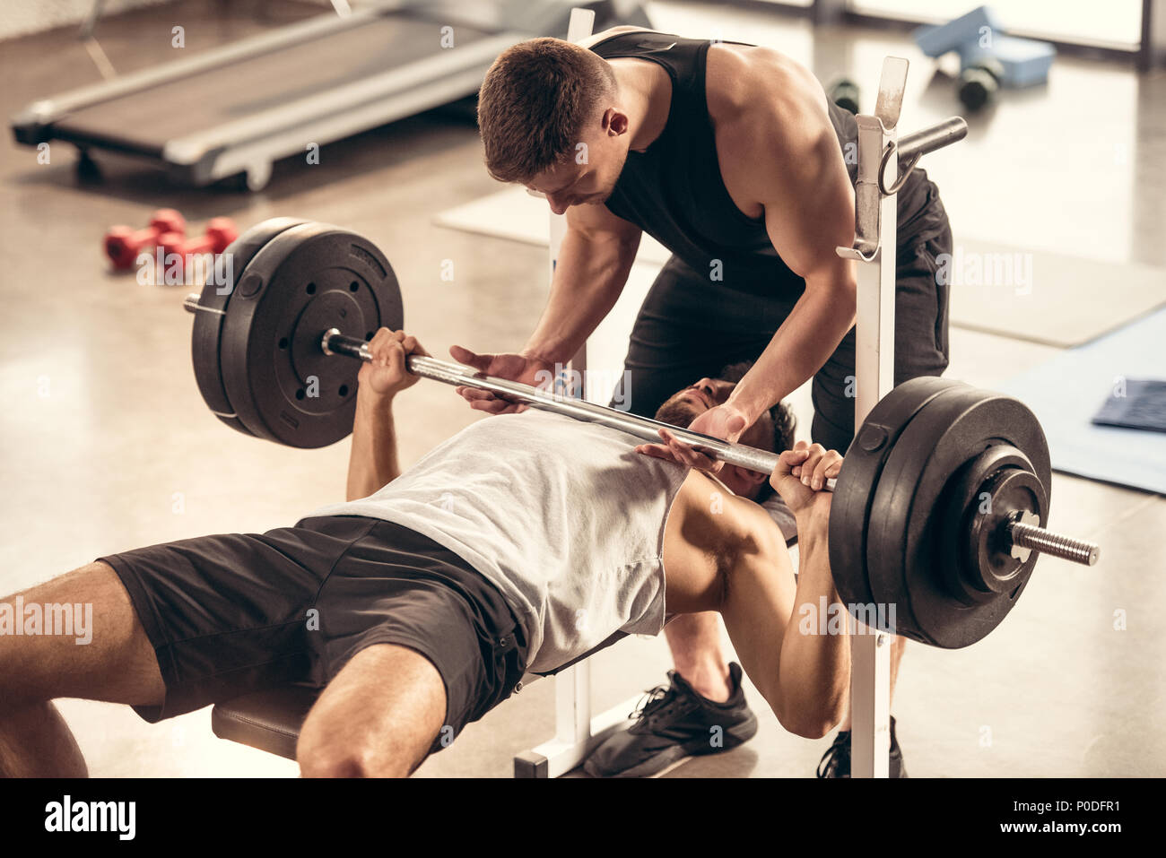 athletic trainer helping sportsman lifting barbell with heavy weight plates in gym - Stock Image