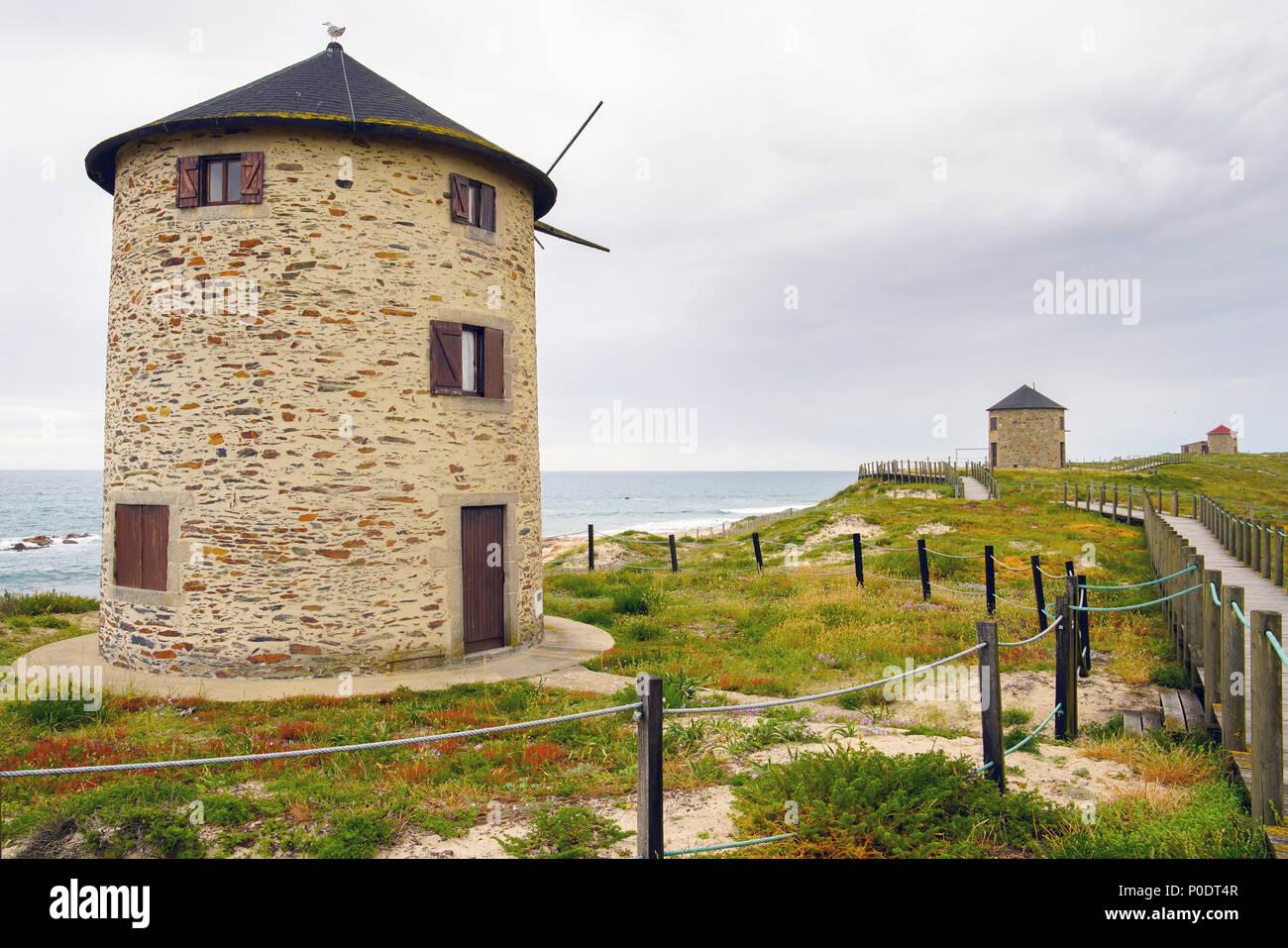 Windmills by the coastal path at beach Praia da Apúlia, Portugal. - Stock Image