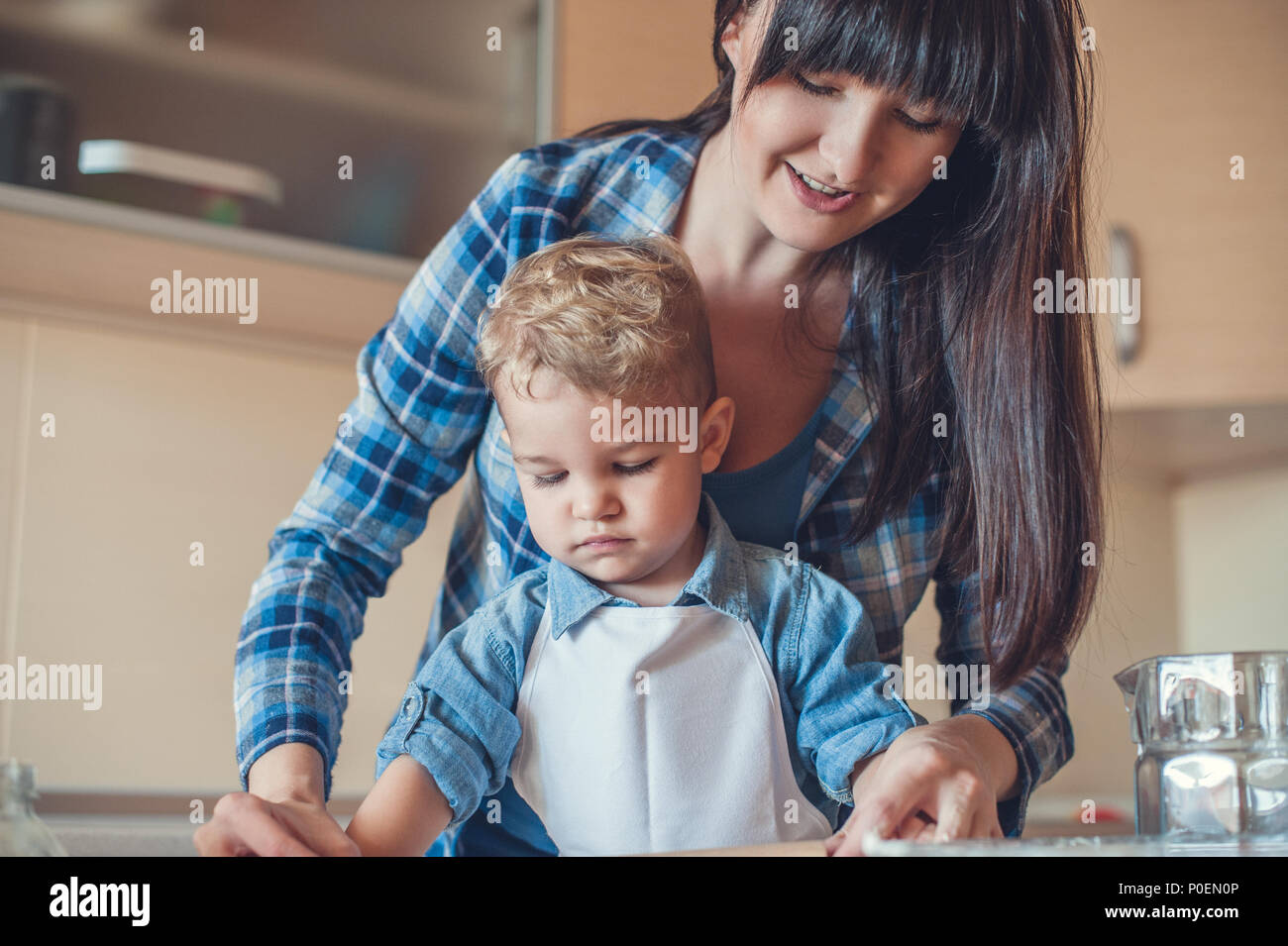 mother and son cooking in kitchen and looking down - Stock Image