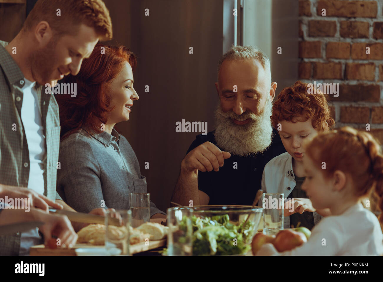happy multigeneration family cooking dinner together at home - Stock Image