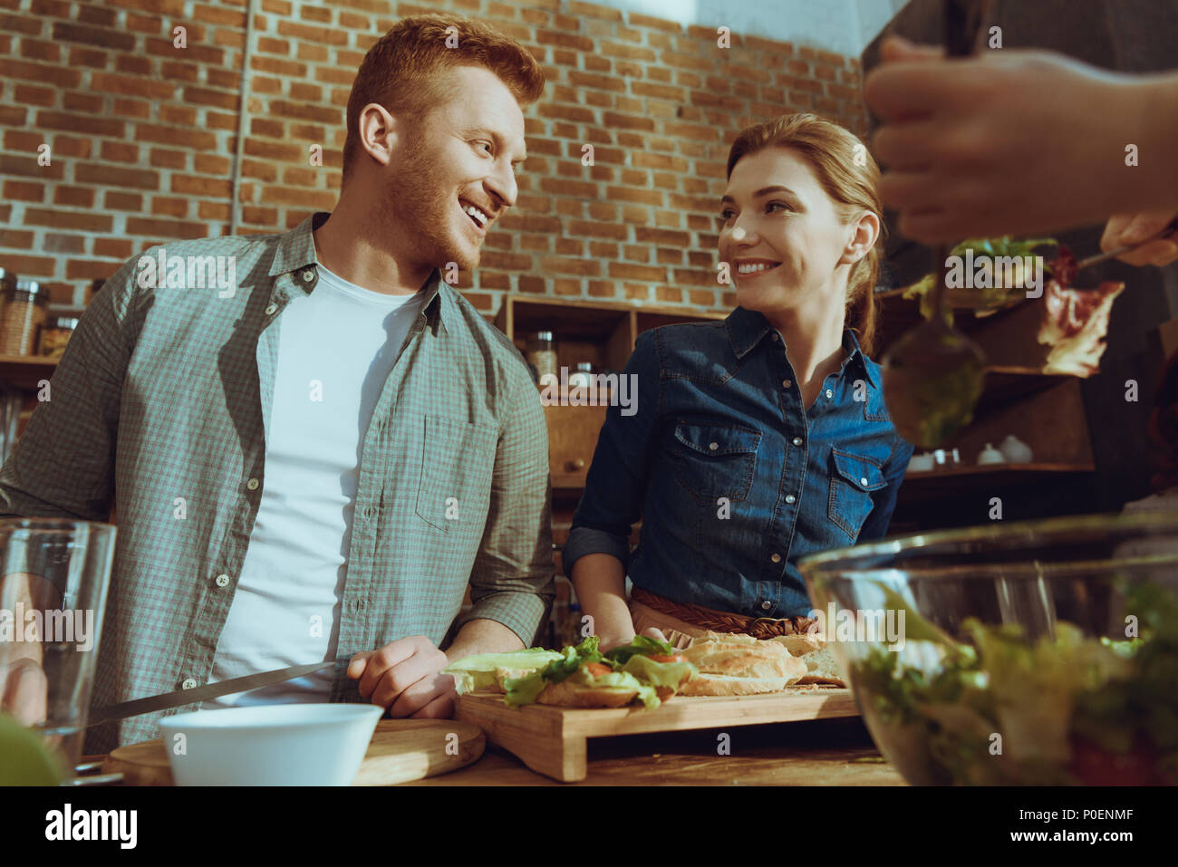 low angle view of smiling couple looking at each other while cooking dinner together at home - Stock Image