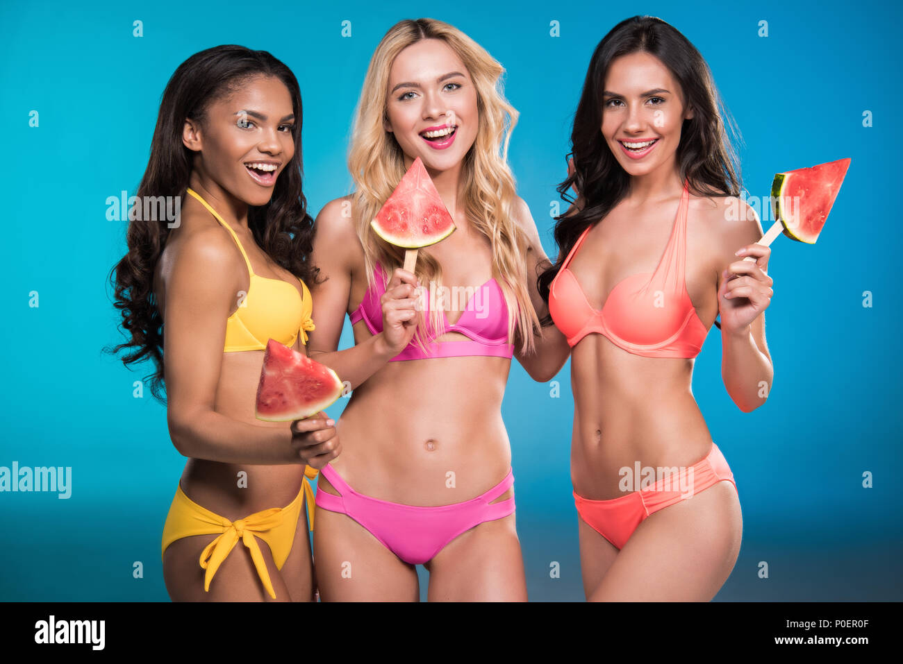 a9c5d31a7f smiling multiethnic girls in swimsuits posing with watermelon slices -  Stock Image