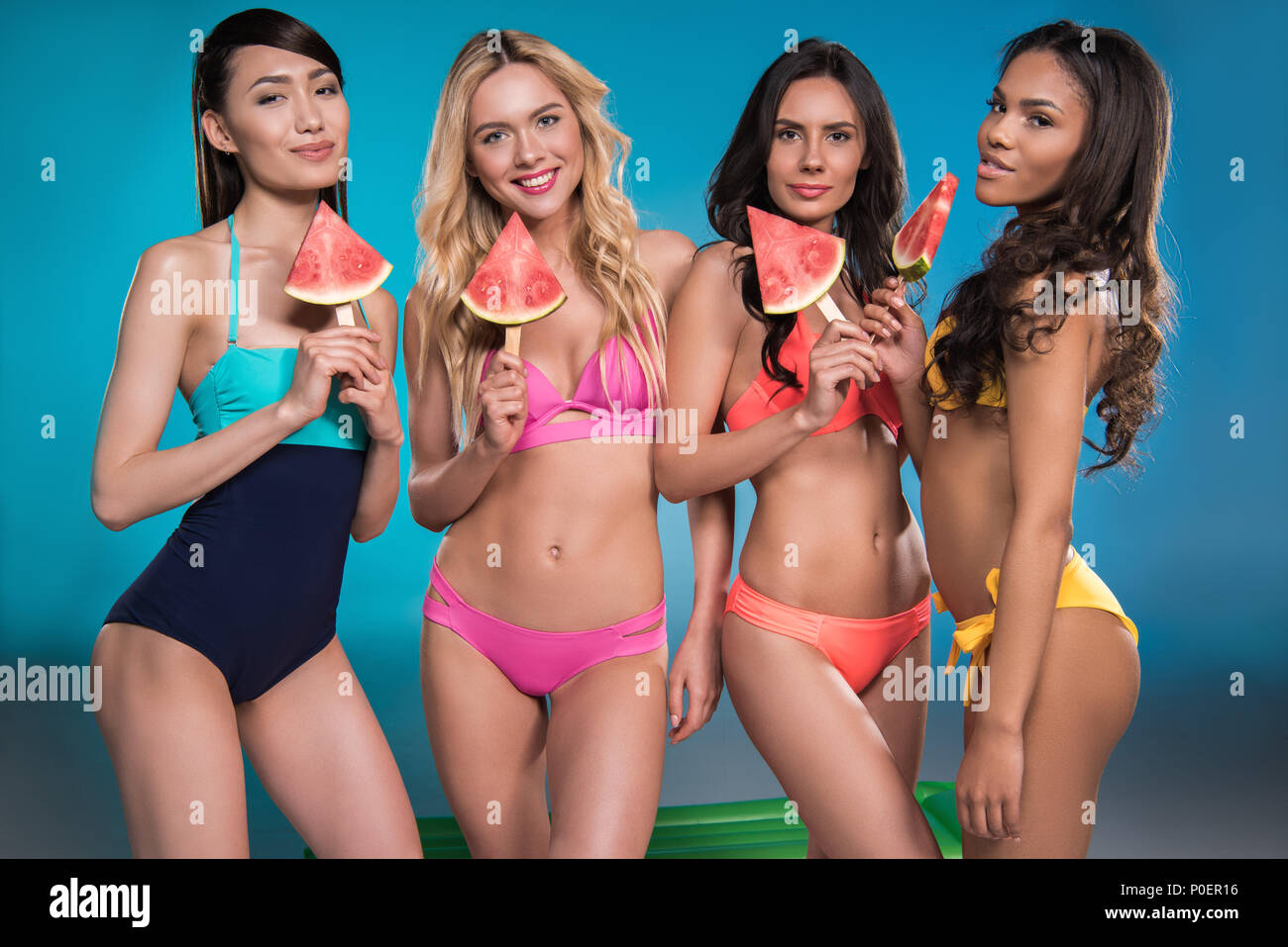 a9f4ca436b multiethnic women in swimsuits smiling and posing with watermelon slices -  Stock Image