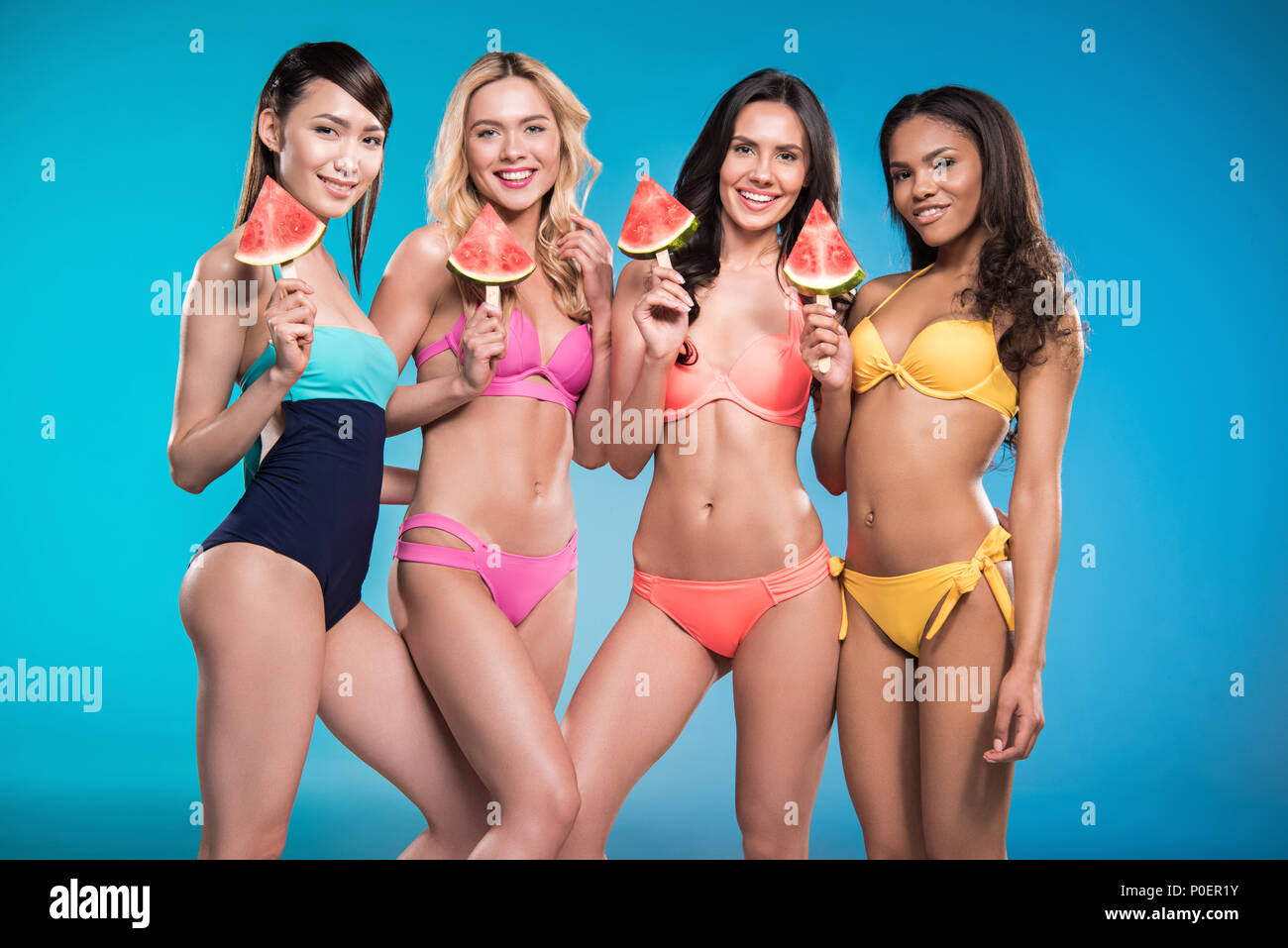 e91d3582cf attractive multiethnic girls in swimsuits posing with watermelon pieces -  Stock Image