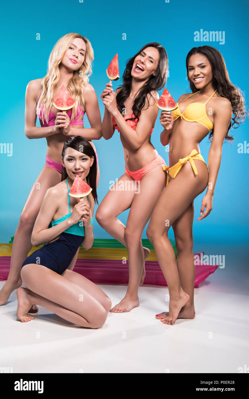 attractive multiethnic women in swimwear smiling and holding watermelon pieces Stock Photo