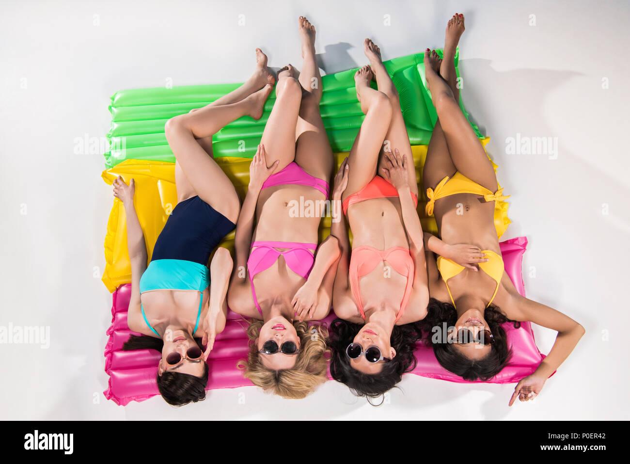 multiethnic girls in swimsuits and sunglasses sunbathing on swimming mattresses - Stock Image