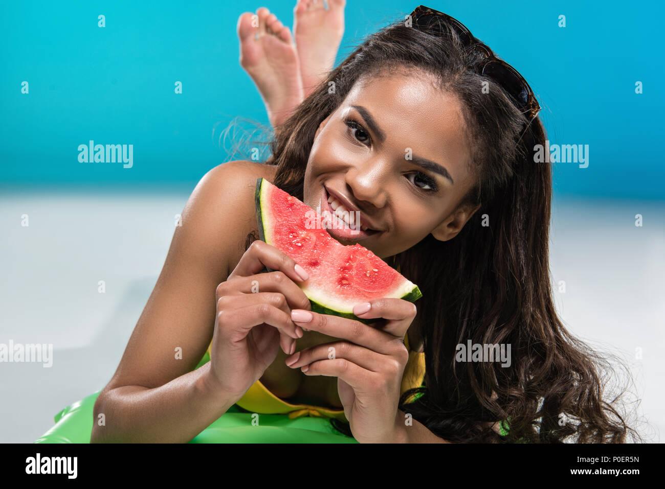 african american girl in swimwear eating watermelon while lying on swimming mattress - Stock Image