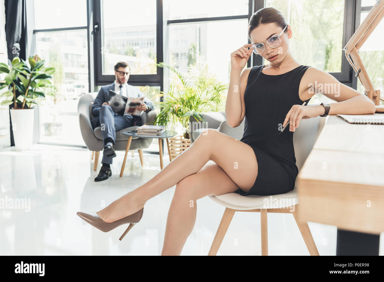 Young businesswoman in black dress and glasses sitting in a chair at office with legs crossed - Stock Image