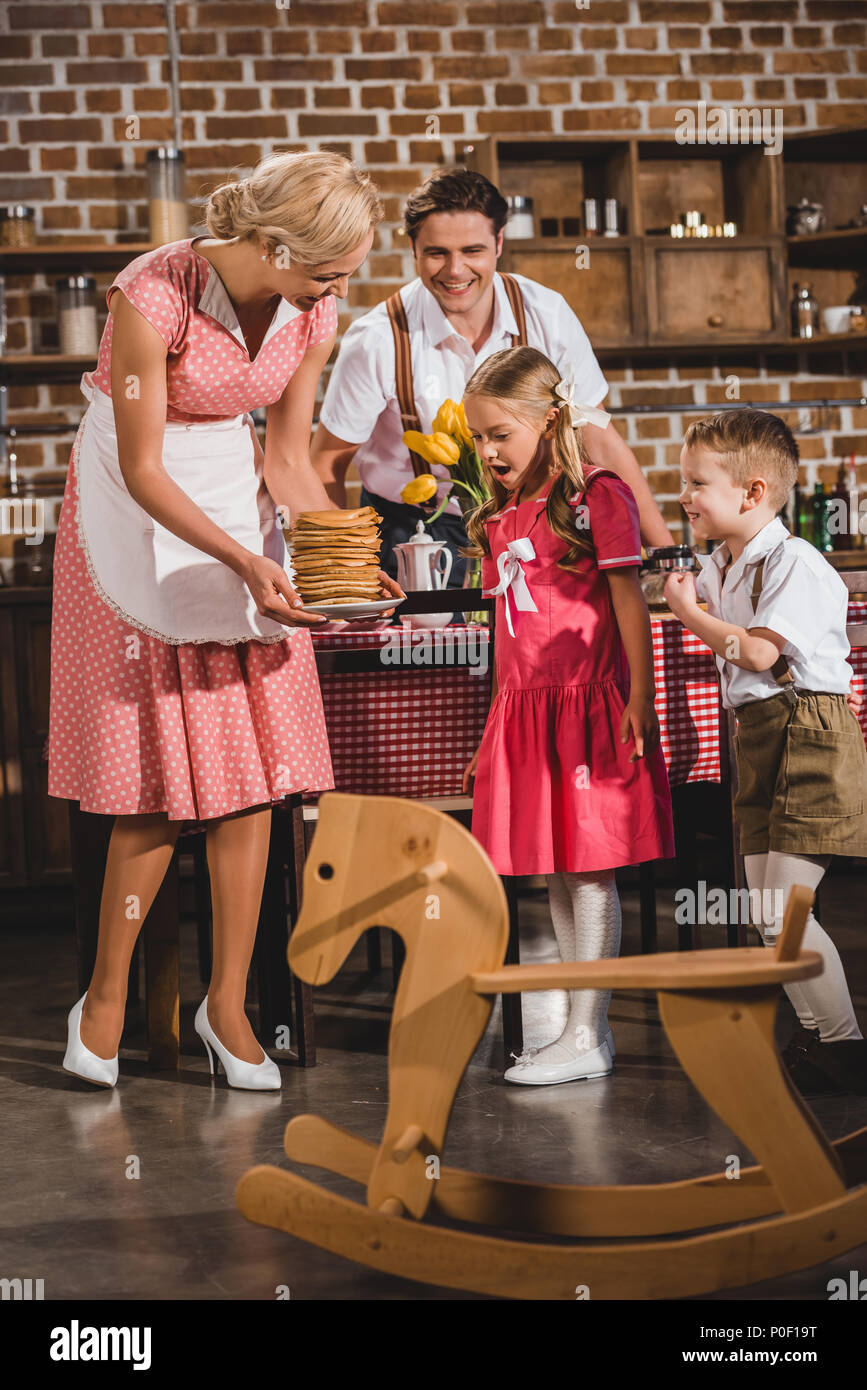 Happy Old Fashioned Family Looking At Smiling Mother Holding Delicious Pancakes Stock Photo Alamy