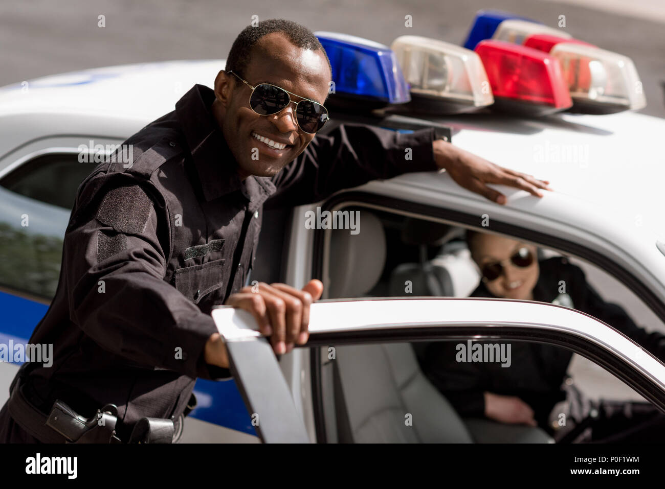 happy young police officers with car looking at camera - Stock Image