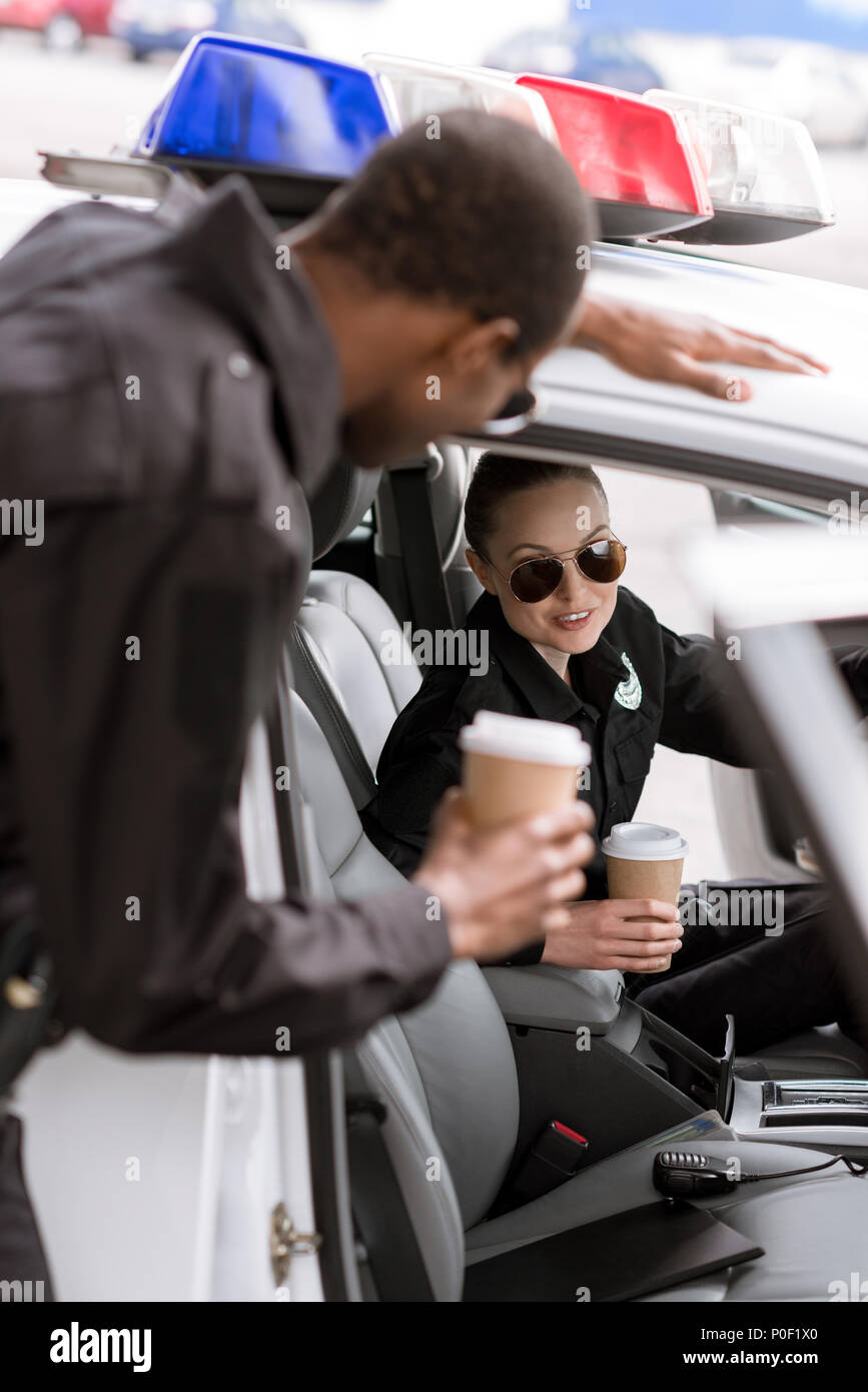 young police officers with car drinking coffee to go - Stock Image