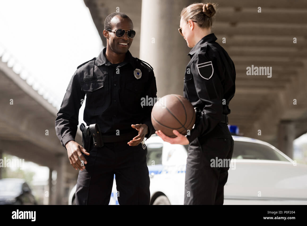 smiling young police officers with basketball ball - Stock Image