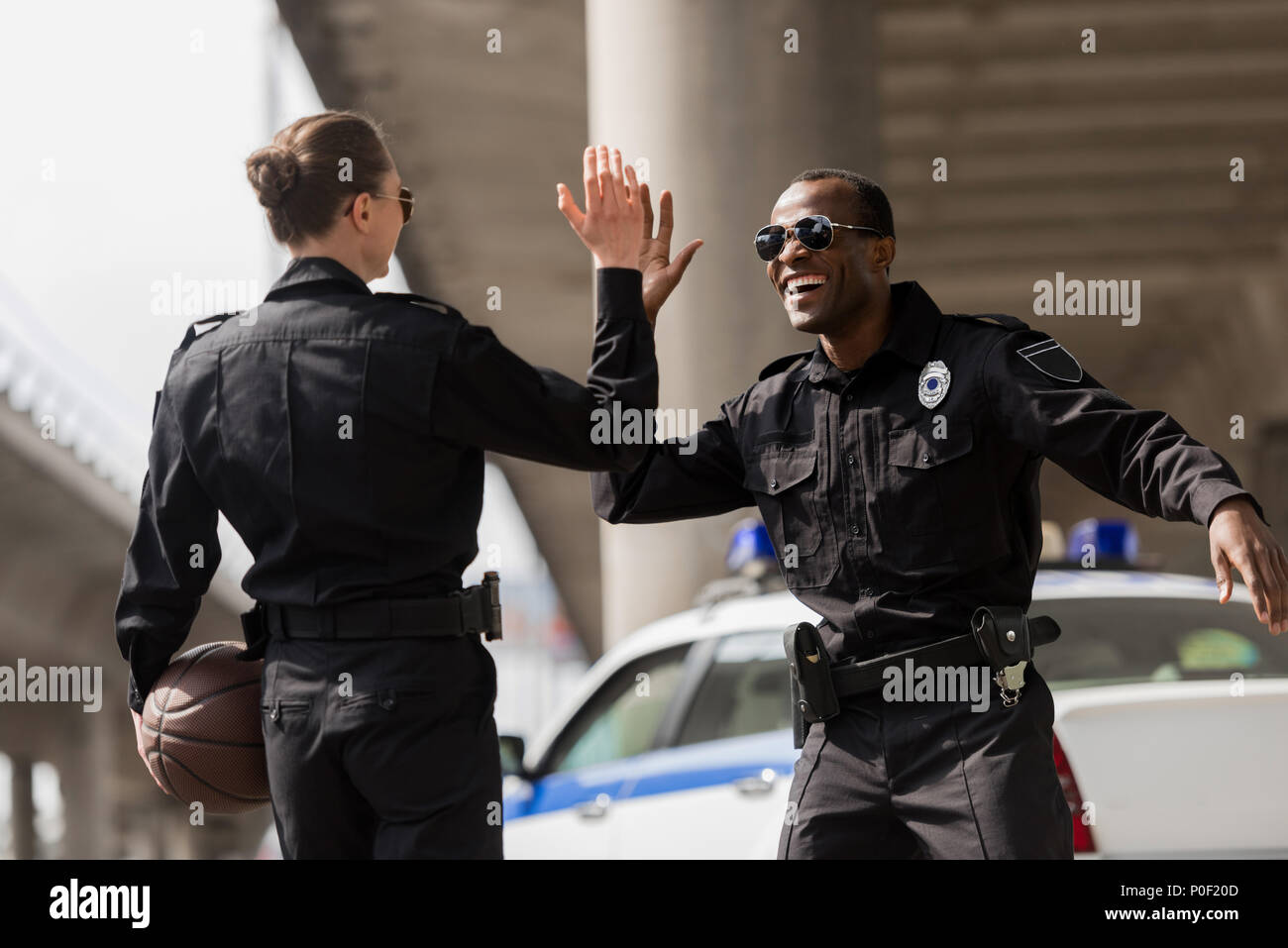 police officers with basketball ball giving high five - Stock Image