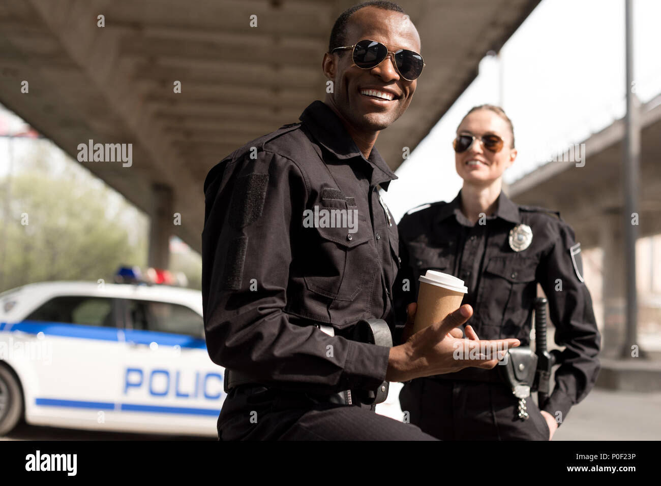 happy young police officers having coffee break - Stock Image