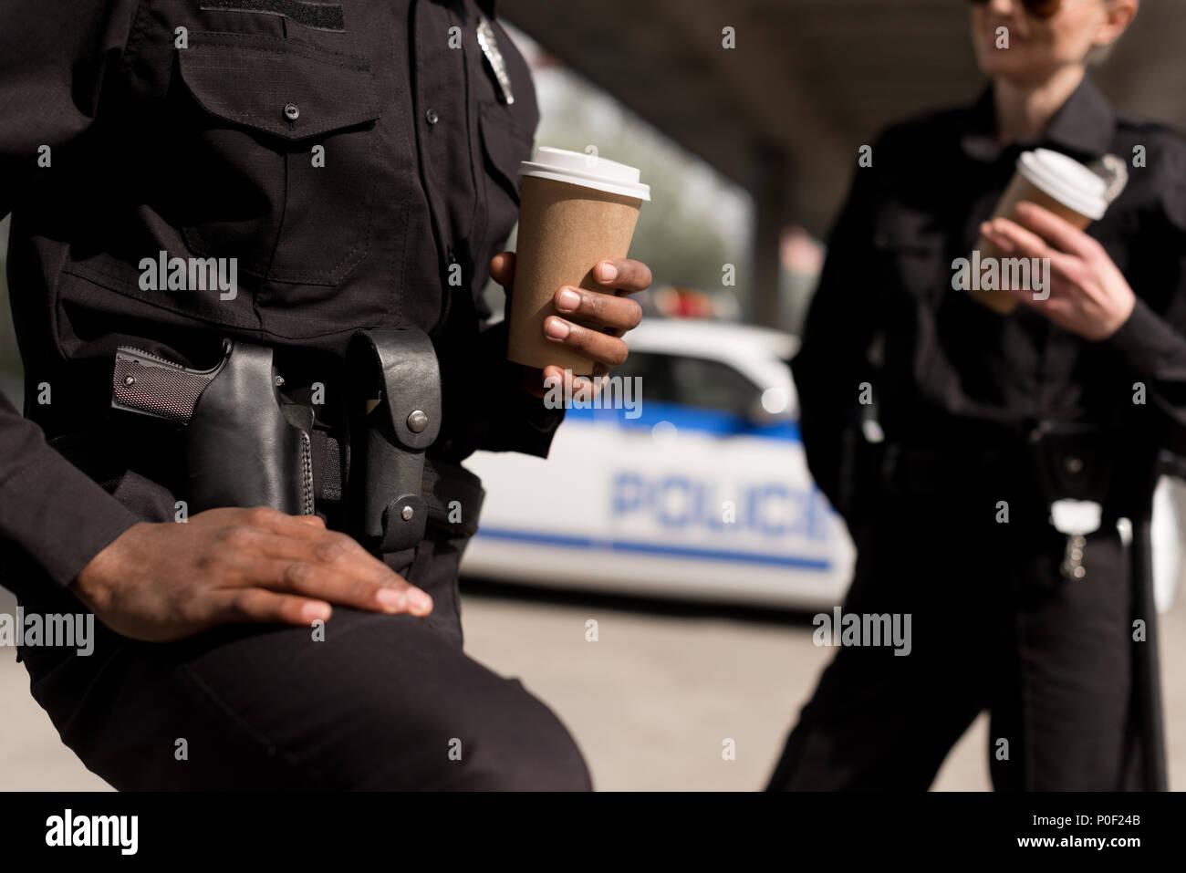 cropped shot of police officers having coffee break - Stock Image