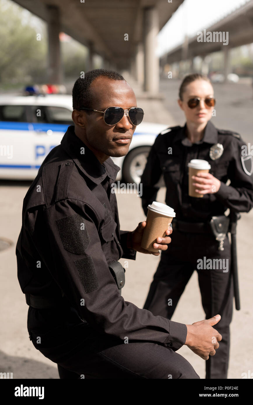 serious young police officers having coffee break - Stock Image