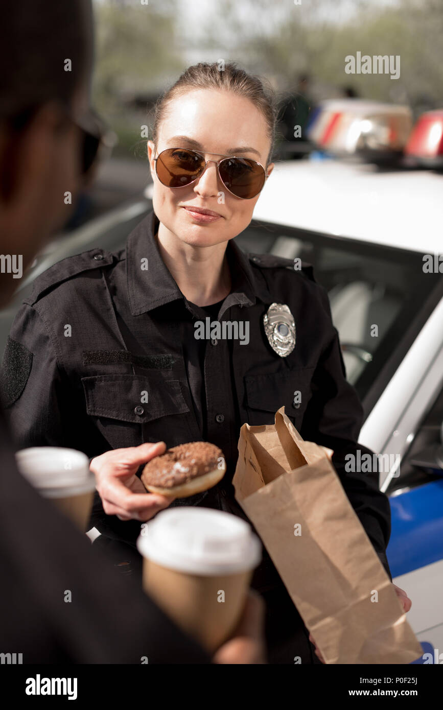 close-up shot of police officers with paper cups of coffee and doughnut - Stock Image