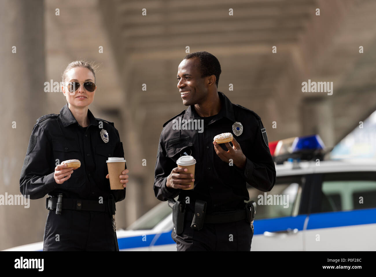 smiling police officers having coffee break with doughnuts - Stock Image