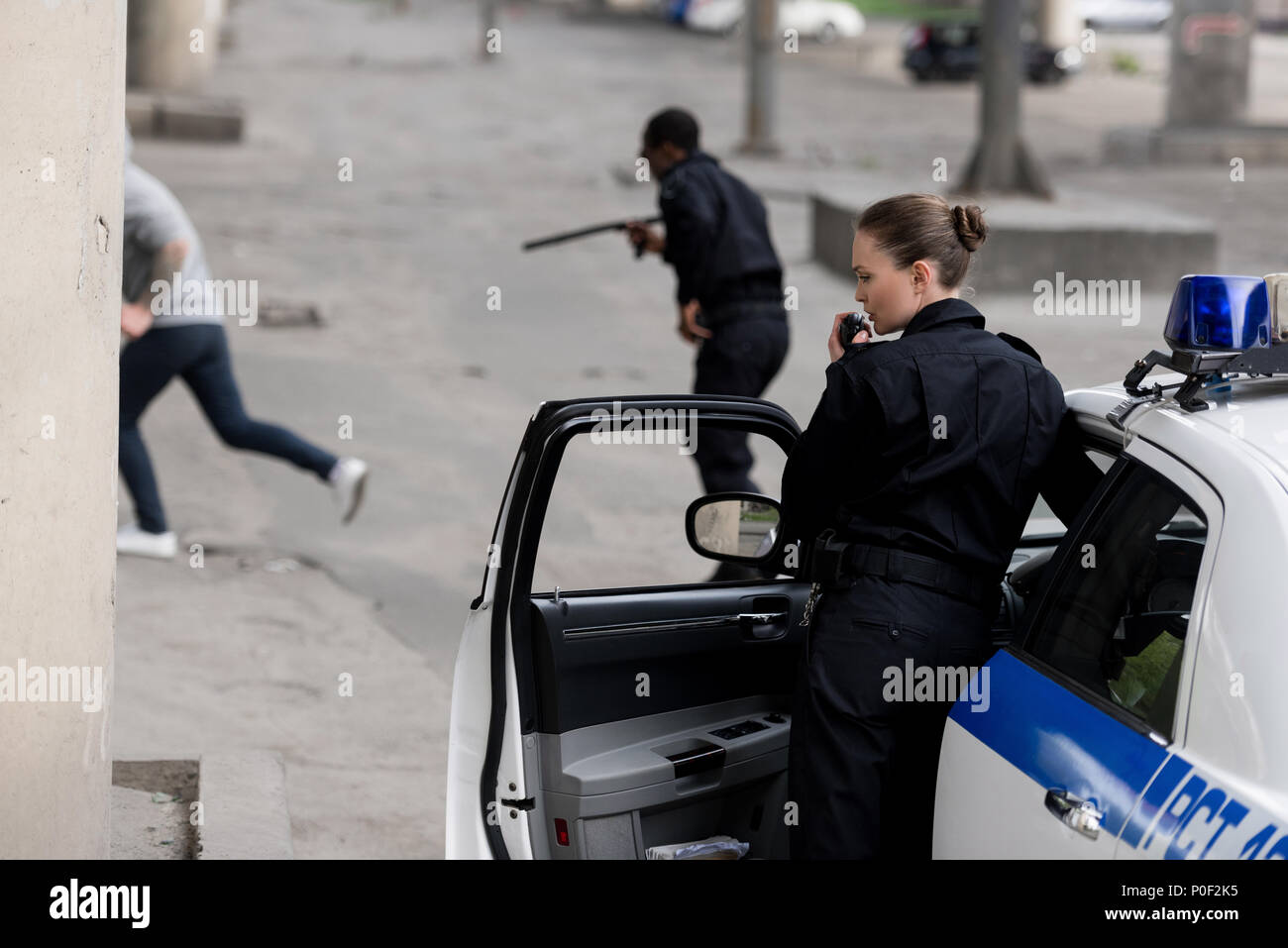 police officers with car chasing thief on street - Stock Image