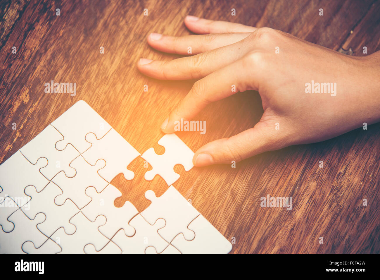 close up of hand placing the last jigsaw puzzle piece hand holding