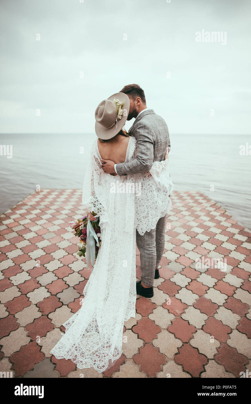 back view of bride and groom in boho style hugging and kissing on pier at lake - Stock Image
