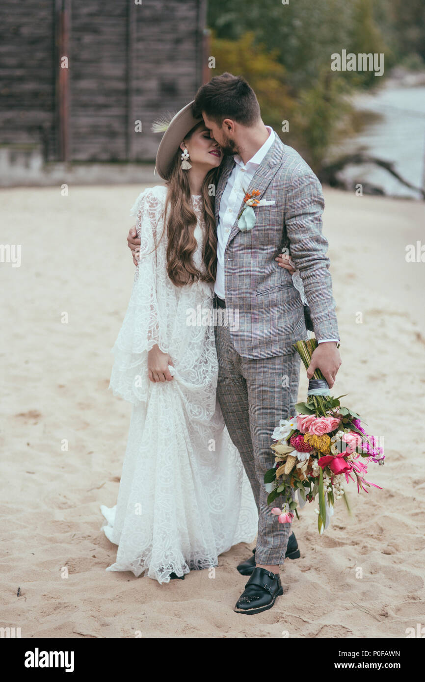 beautiful bride and groom in boho style kissing on beach - Stock Image