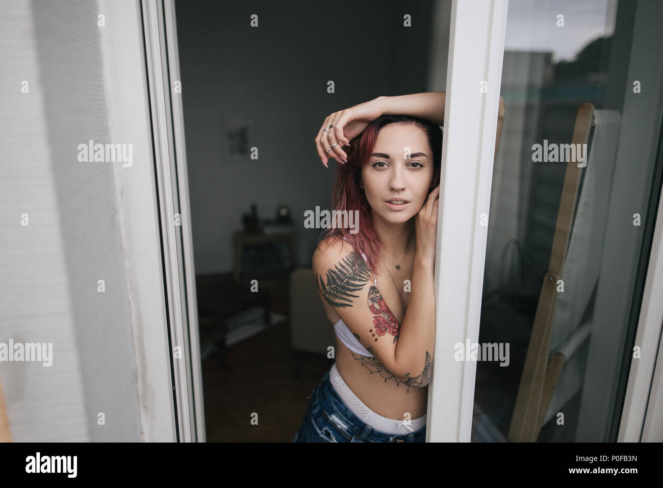 d31e2f7596b beautiful tender young woman in bra and denim shorts looking at camera  through open window -