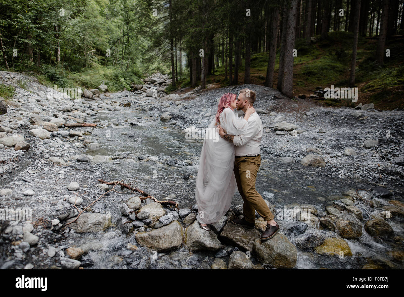 beautiful young wedding couple kissing while standing on rocks in rapid mountain river, Alps - Stock Image