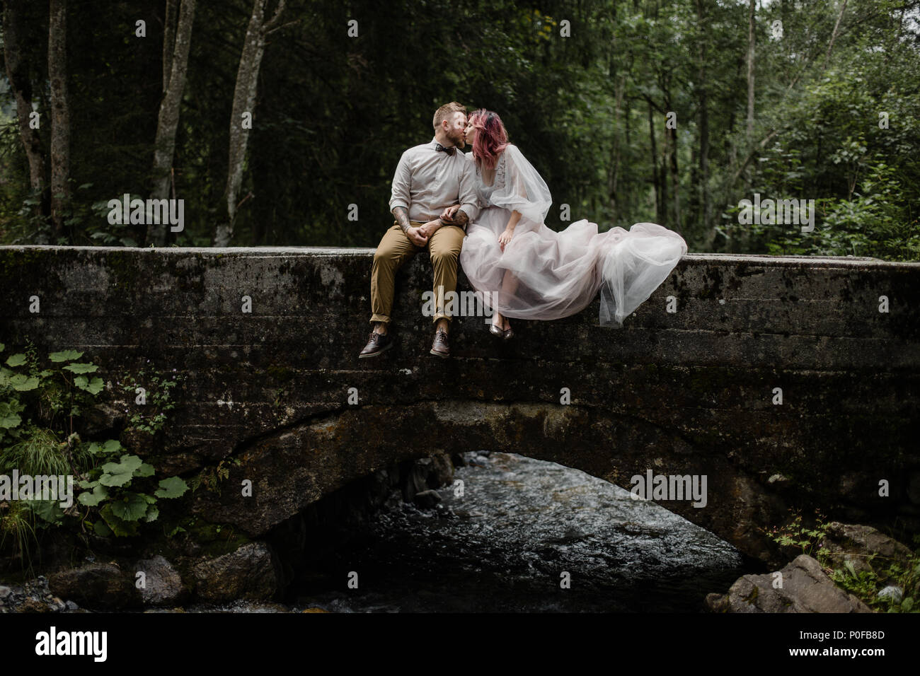 beautiful young wedding couple kissing while sitting on bridge above mountain river in Alps - Stock Image