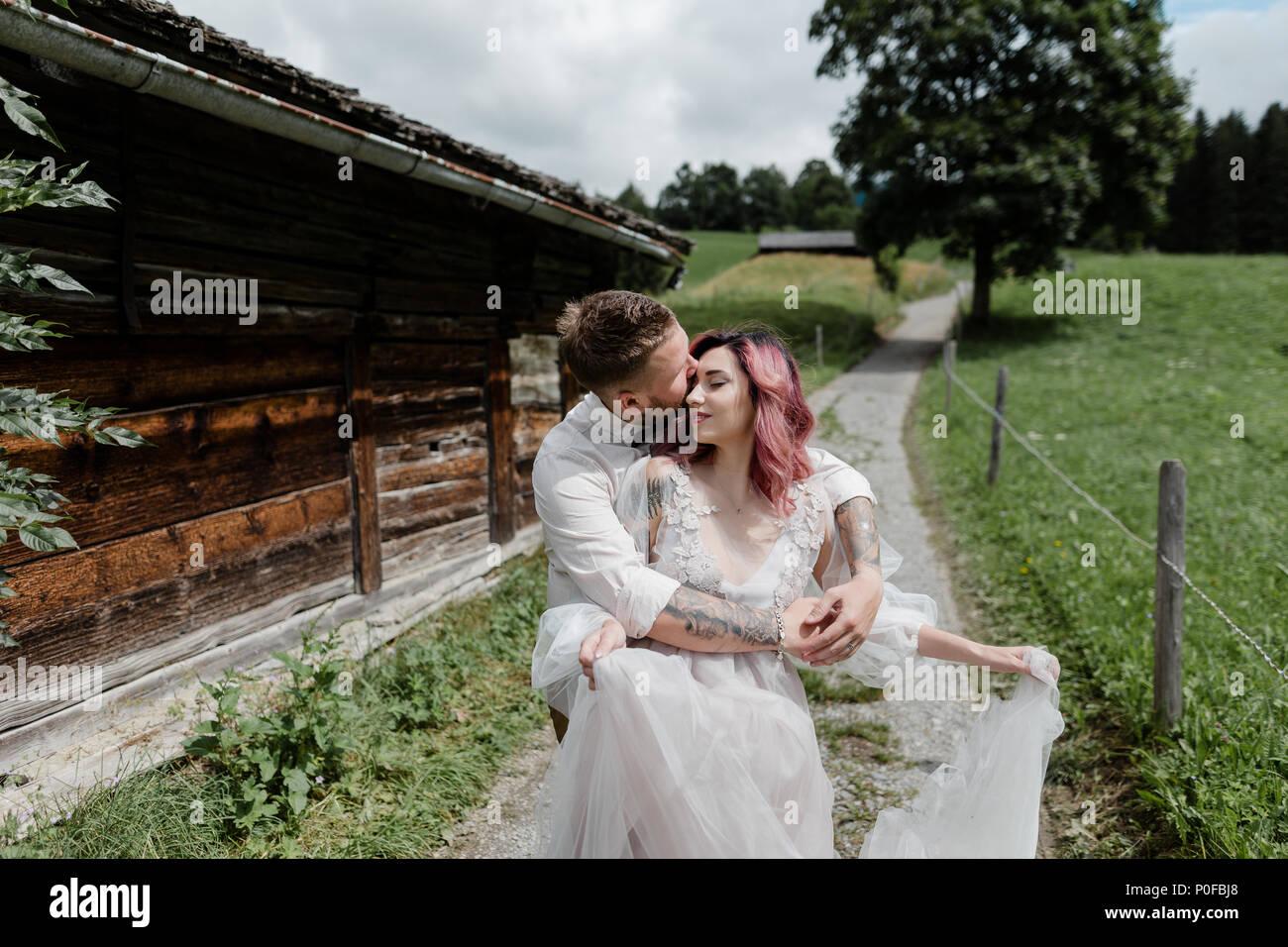 handsome groom kissing and hugging bride in wedding dress, Alps - Stock Image