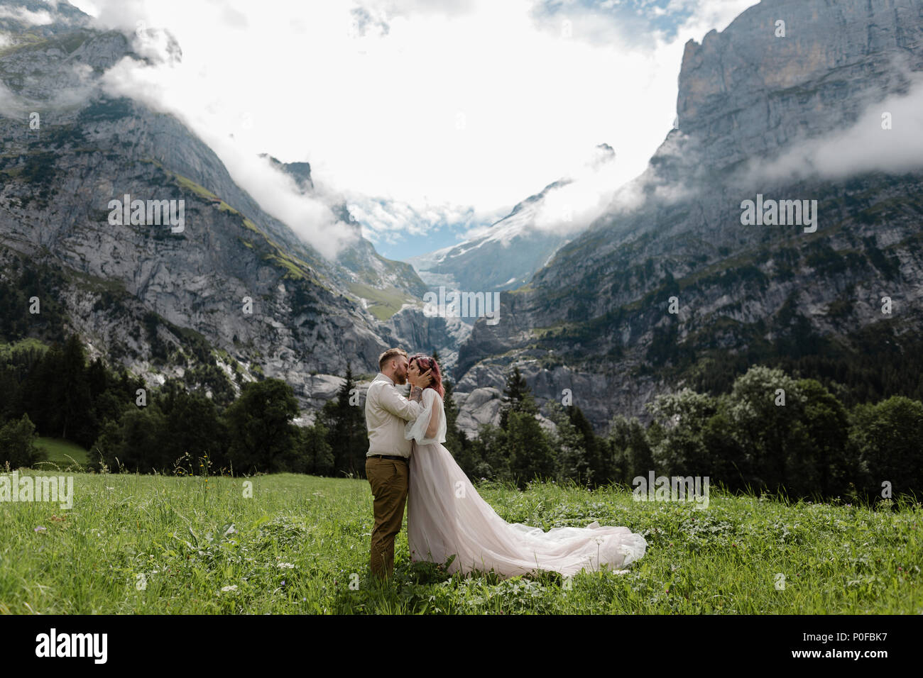 happy bride and groom hugging and kissing on green mountain meadow with clouds in Alps - Stock Image