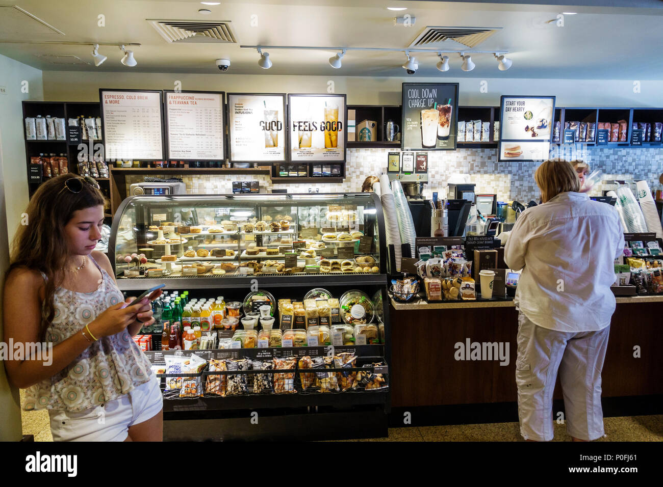 Florida Palm Beach Worth Avenue Esplanade shopping center Starbucks Coffee coffeehouse interior counter woman young adult using smartphone Stock Photo