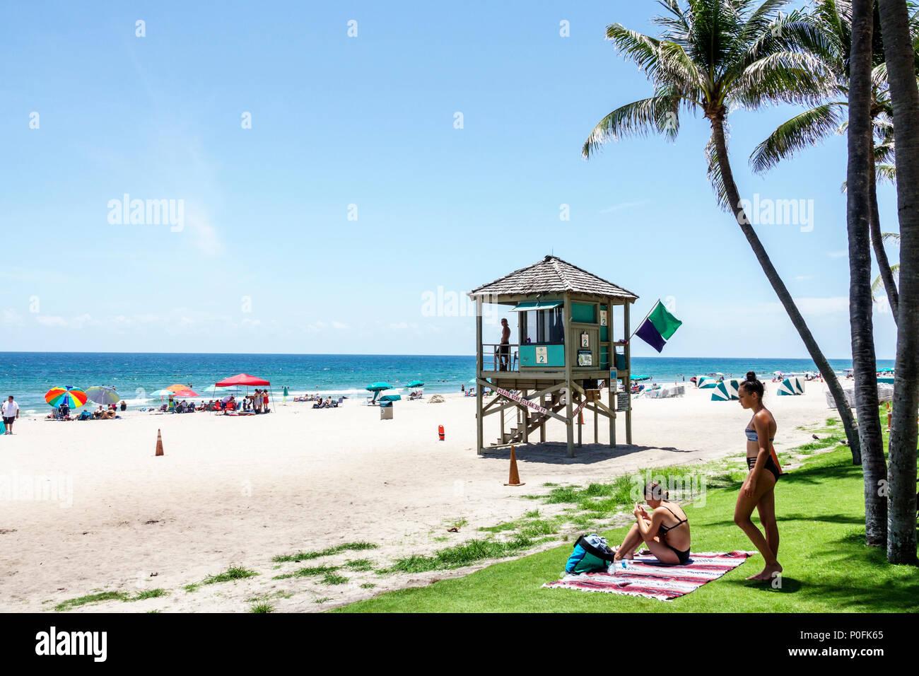 Florida Atlantic Ocean Deerfield Beach water sand lifeguard tower palm trees woman sunbather - Stock Image