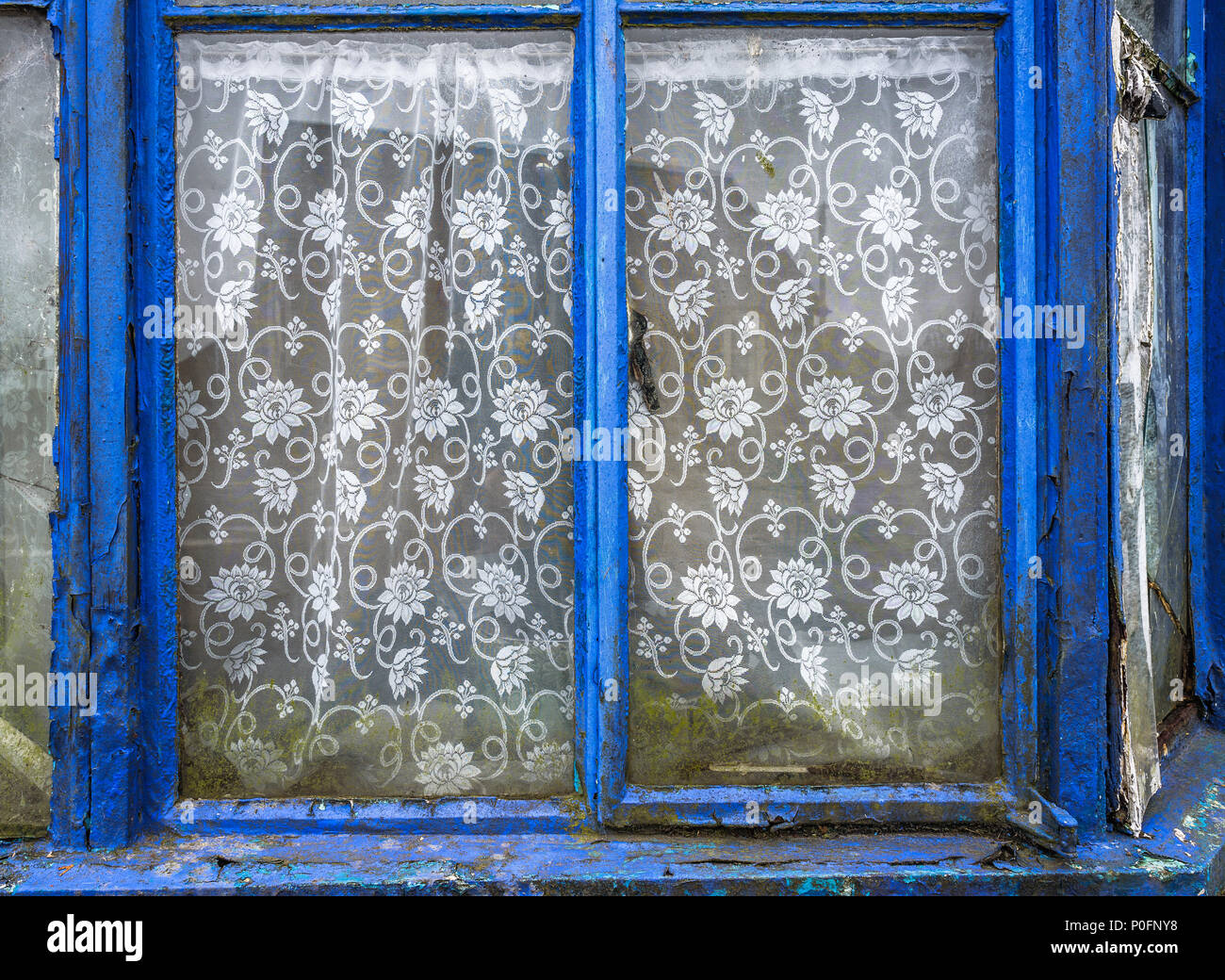Old abandoned house with weathered window frames and net curtains. - Stock Image