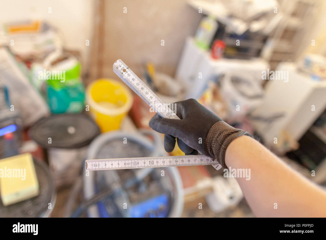 Hand holds a german double meter stick on a construction site - Stock Image